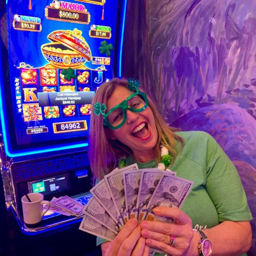 Deanne smiling as she holds her winnings of $849