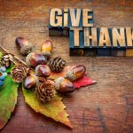 The words Give Thanks next to leaves, acorns, and pine cones