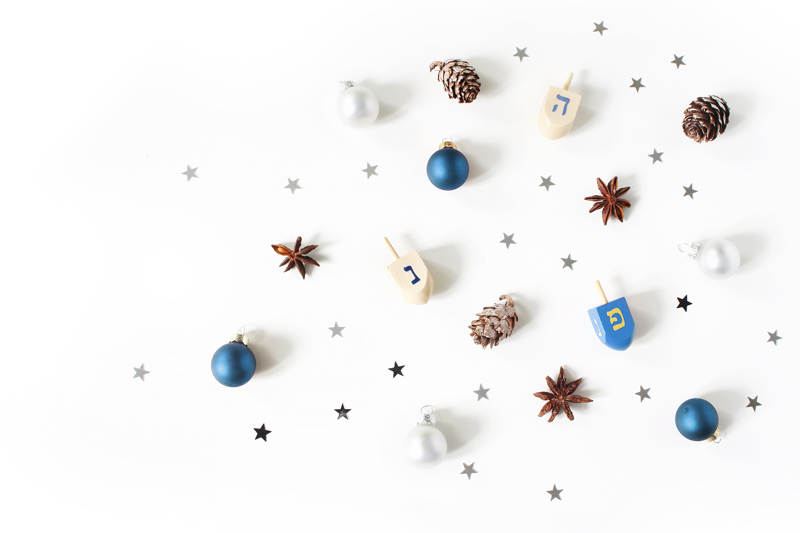 Dreidels next to stars, pinecones, and ornaments