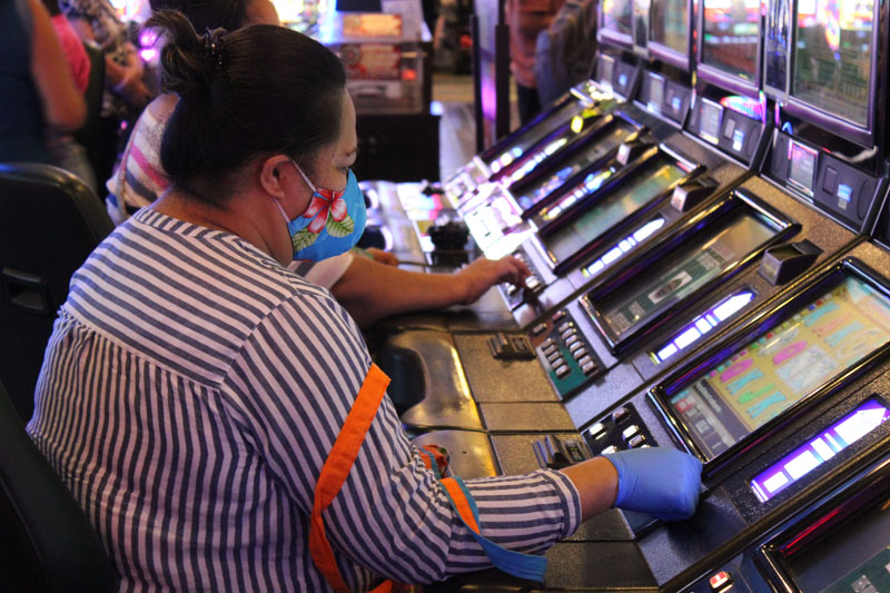 customer at machine with mask and gloves